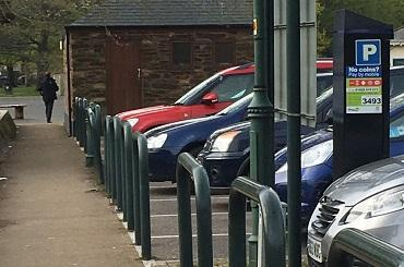 A line of parked cars in a public car park