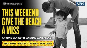 A father and young son on a beach with the message this weekend give the beach a miss.