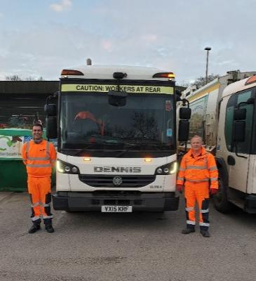 Two male waste collection workers wearing orange high viz clothing and posing next to a waste collection vehicle.