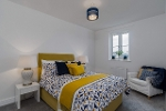 A photograph showing an example of a double bedroom in the new development at Sherford. There is a double bed decorated in yellow and blue bedding, with a sofa in the corner and a bedside table. The room is painted white with a grey carpet.