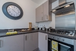 An image showing an example of a kitchen in the new build properties at Sherford. The fitted cupboards are grey, and there is a stainless steel gas hob over the oven. There is a large decorative clock on the wall.