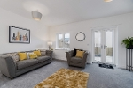 An example of the sitting room in the new build properties at Sherford. The large room has a window and patio door, and a grey carpet with a bright yellow rug. There is a sofa and arm chair with yellow throw cushions.