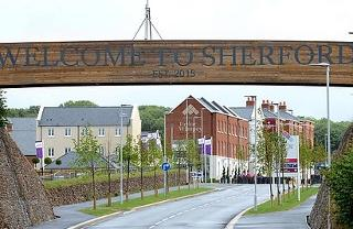 A photograph of the main road entering Sherford, with a banner above it reading 'Welcome to Sherford'