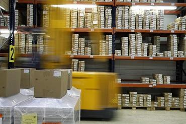 A yellow forklift truck moving through a warehouse